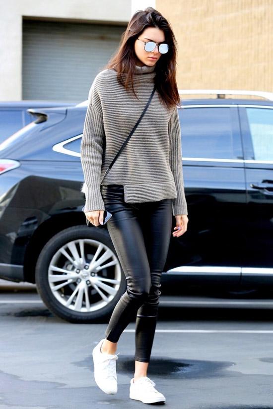 Девушка в черных леггинсах, серы свитер и белые кеды