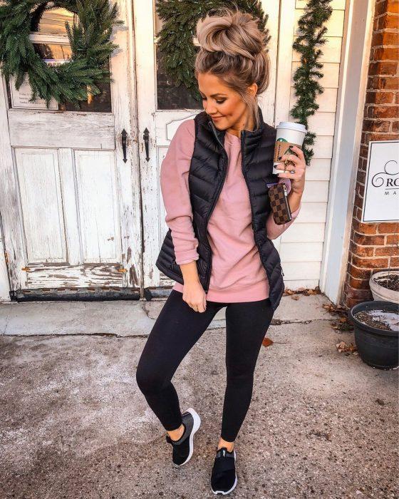 Девушка в черных лосинах, розовый джемпер и черный жилет