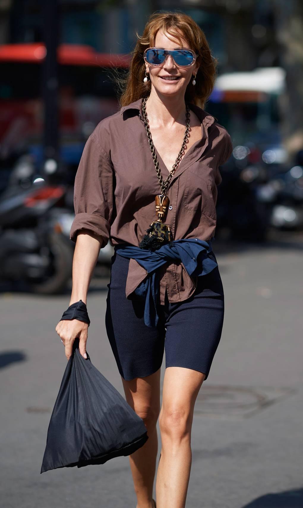 Девушка в черных вело шортах и коричневой рубашке