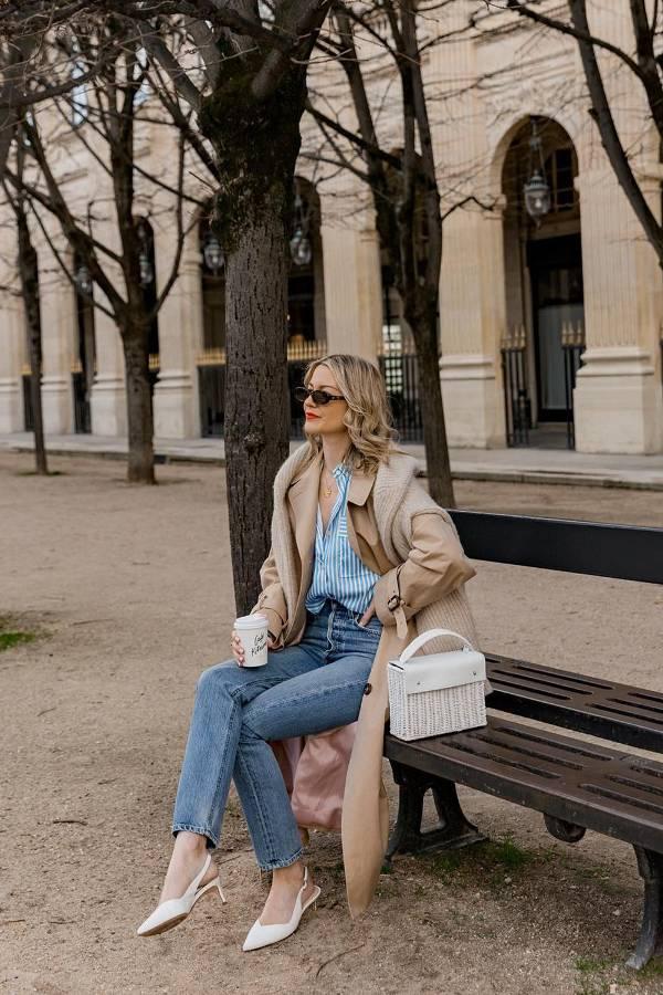 Девушка в джинсах, рубашка в полоску, бежевое пальто и белые туфли