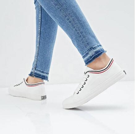 Девушка в джинсах и белых кедах