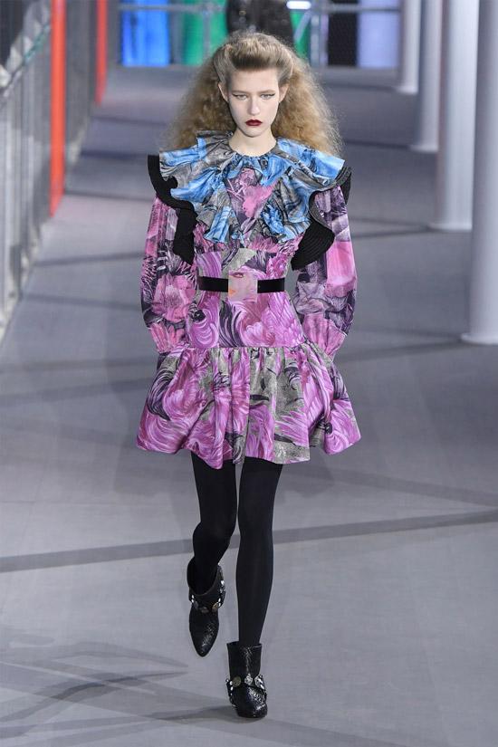 Девушка в фиолетом платье мини с рюшами, черные колготки и ботильоны