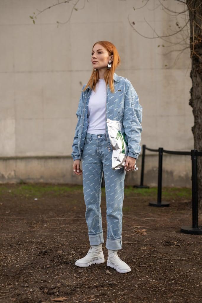 Девушка в голубом костюме из денима и белых кроссовках