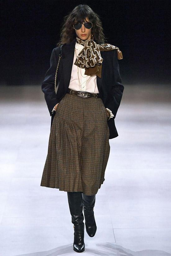 Девушка в коричневой юбке миди, черный блейзер и сапоги