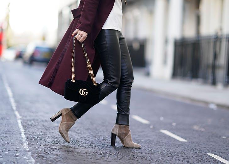 Девушка в кожанных брюках и коричневых ботильонах на каблуке