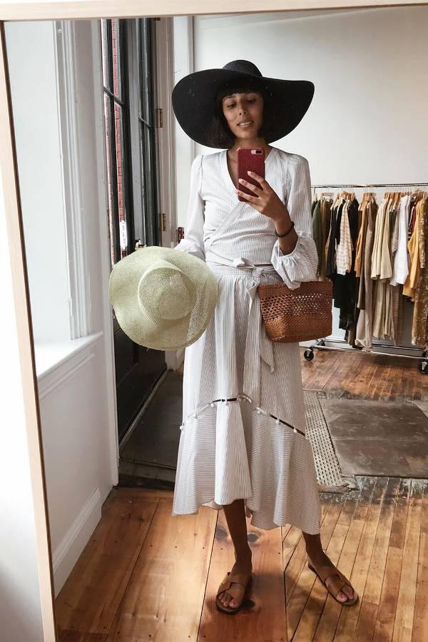 Девушка в легком белом платье, черная шляпа и коричневык шлепки