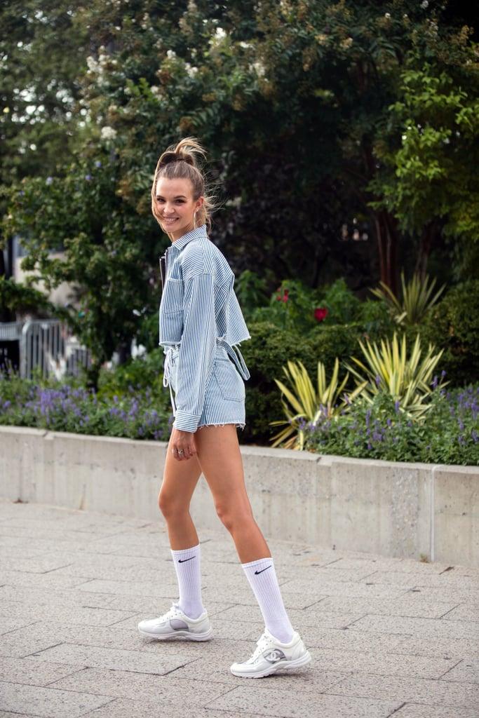 Девушка в мини шортах укороченный жакет и кроссовки