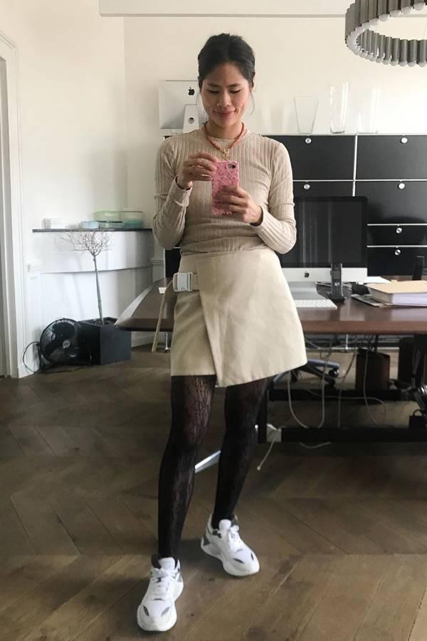 Девушка в мини юбке, бежевая водолазка и белые кроссовки