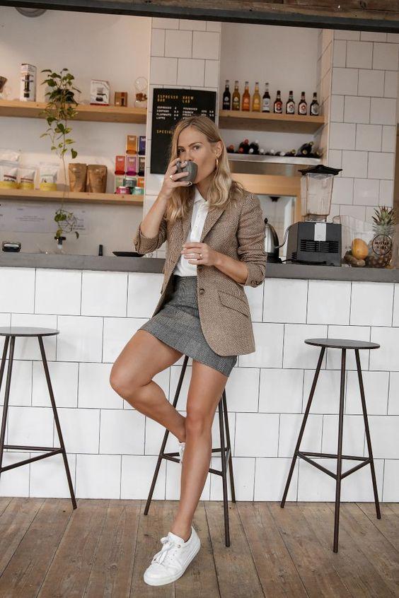 Девушка в мини юбке, коричневый блейзер и белые кеды