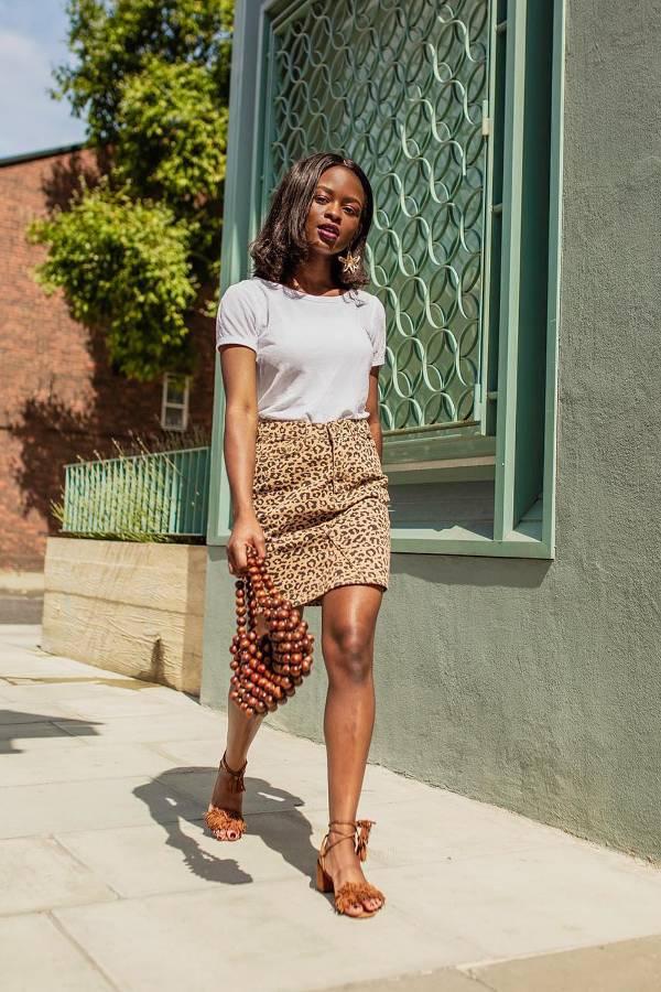 Девушка в мини юбке с леопардовым принтом, белая футболка и коричневые босоножки