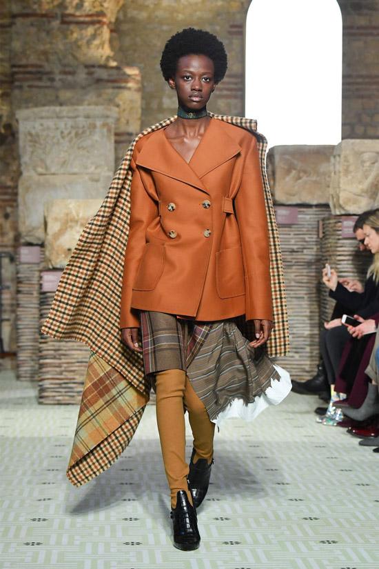 Девушка в оранжевом пальто, клетчатая накидка и черные ботинки