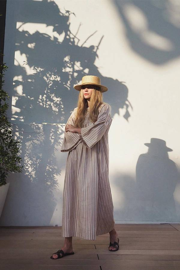 Девушка в просторном платье в полоску, соломенная шляпа и сандалии