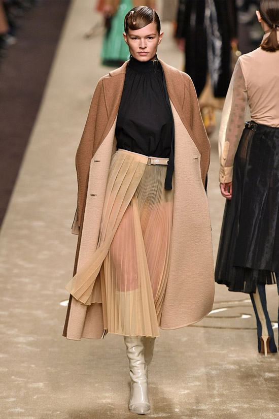 Девушка в прозрачной юбке миди, черная водолазка и коричневое пальто