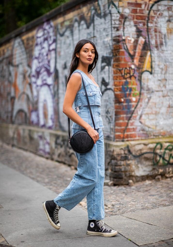 Девушка в прямых джинсах и топ, черные кеды