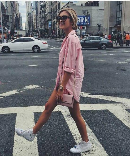 Девушка в розовой рубашке оверсайз и белые кеды
