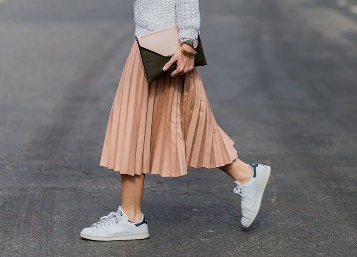 Девушка в розовой юбке миди и белых кедах