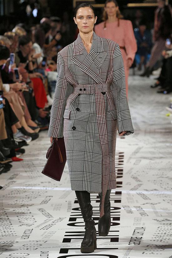 Девушка в сером пальто в клетку с поясом