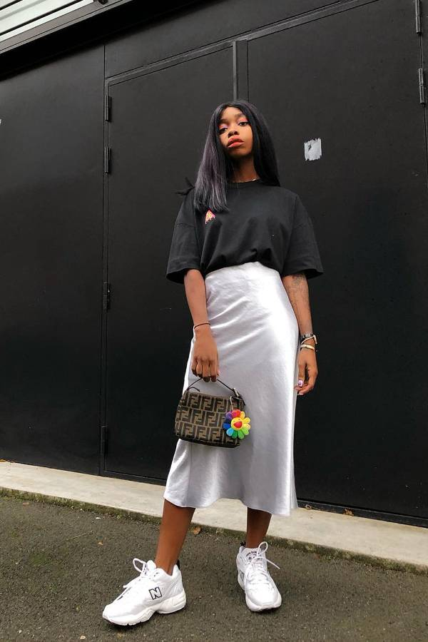 Девушка в серой шелковой юбке,черная футболка и белые кроссовки