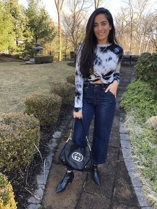 Девушка в серой толстовке, широкие синие джинсы и ботильоны