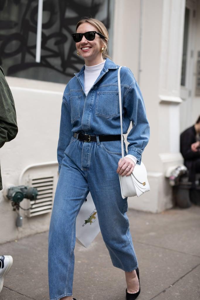 Девушка в синем джинсовом комбинезоне с ремнем и белая водолазка