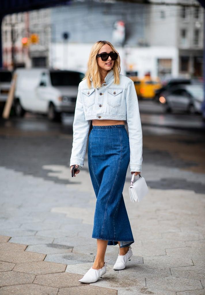 Девушка в синей джинсовой юбке и белой укороченной курткой