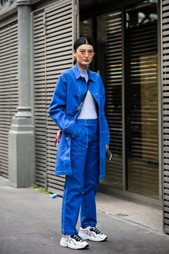 Девушка в синих джинсах и джинсовый плащ, кроссовки