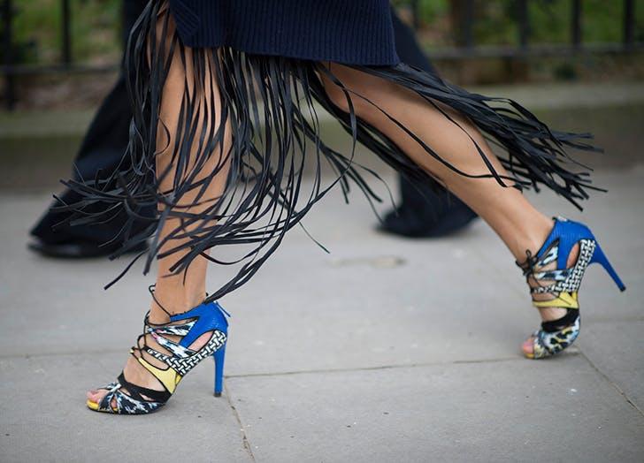 Девушка в синих туфлях на шпильке и юбке с бахромой