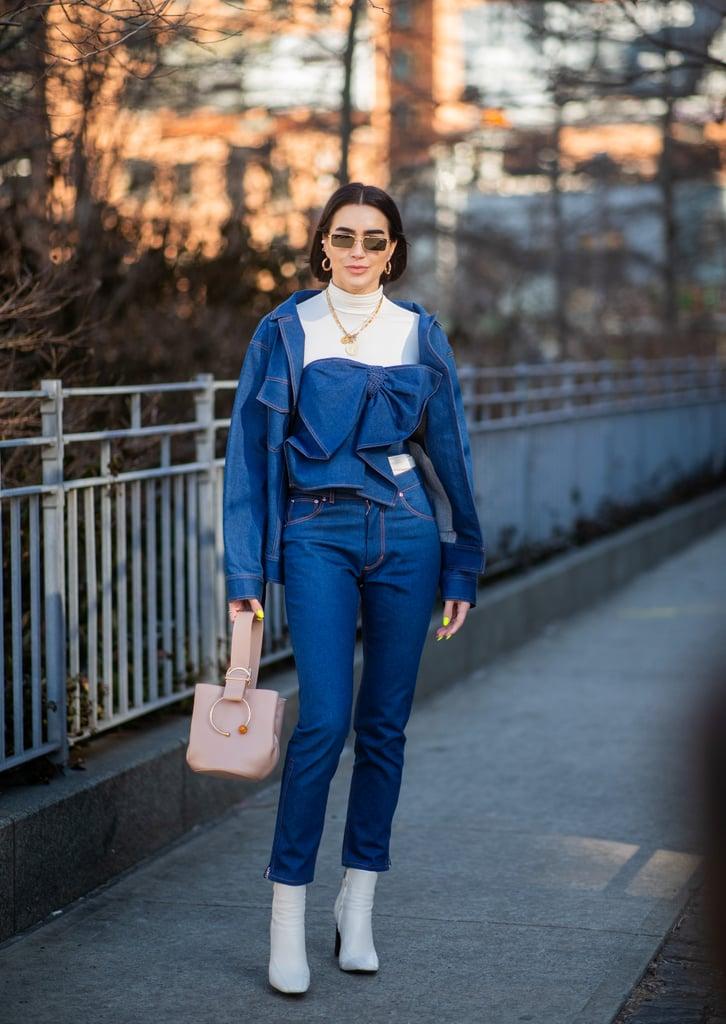 Девушка в синих укороченных джинсах, жакет и белые ботильоны