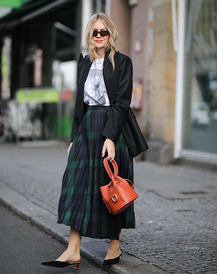 Девушка в темной юбке миди, футболка и черный жакет