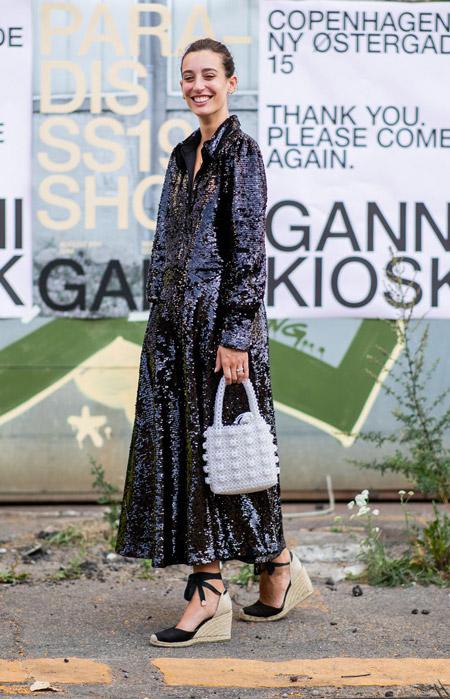 Девушка в вечернем платье с блестками, босоножки на танкетке и белая сумочка