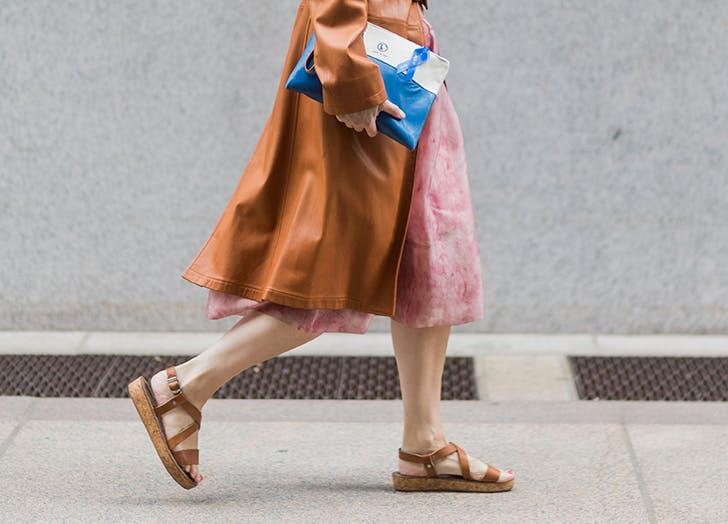Девушка в юбке миди и коричневых сандалиях