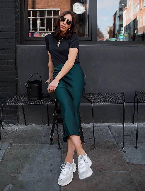 Девушка в зеленой облегающей юбке, черная футболка и белые кроссовки