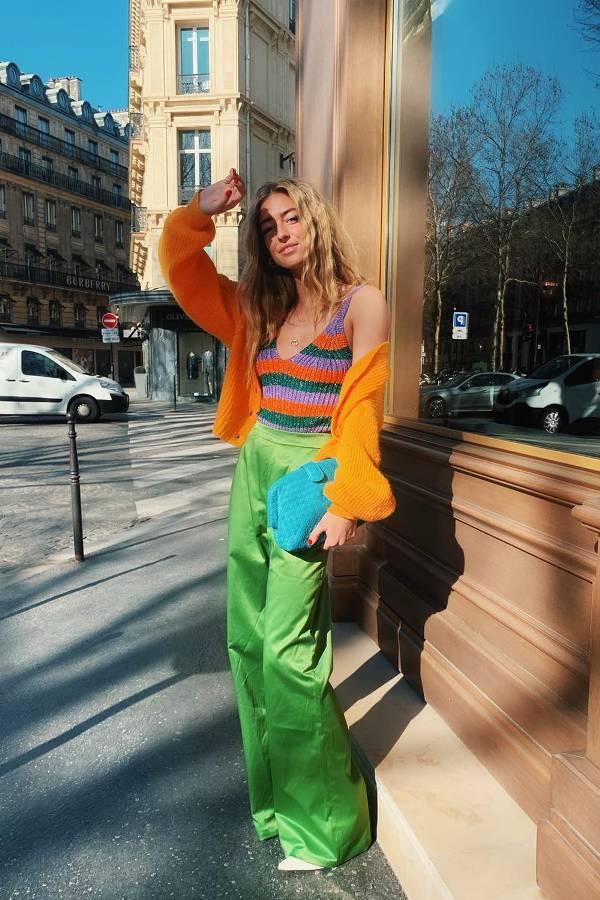 Девушка в зеленых брюках, разноцветный топ и белые туфли