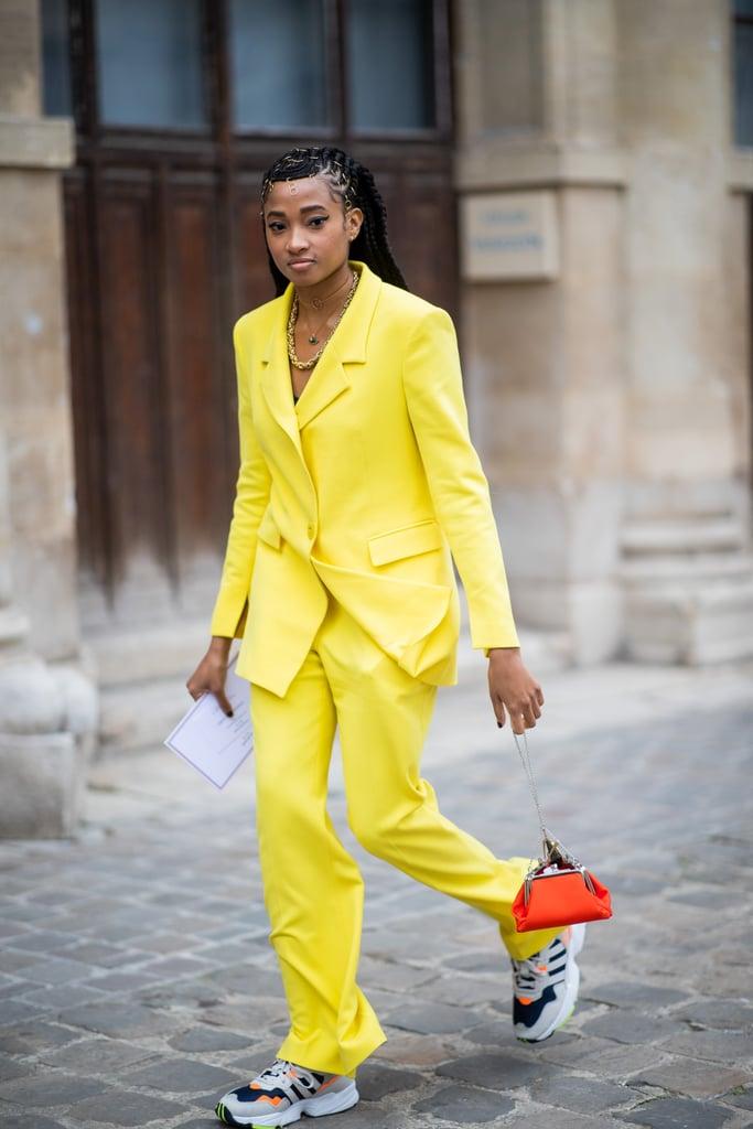 Девушка в желтом брючном костюме, кроссовки и мини сумочка