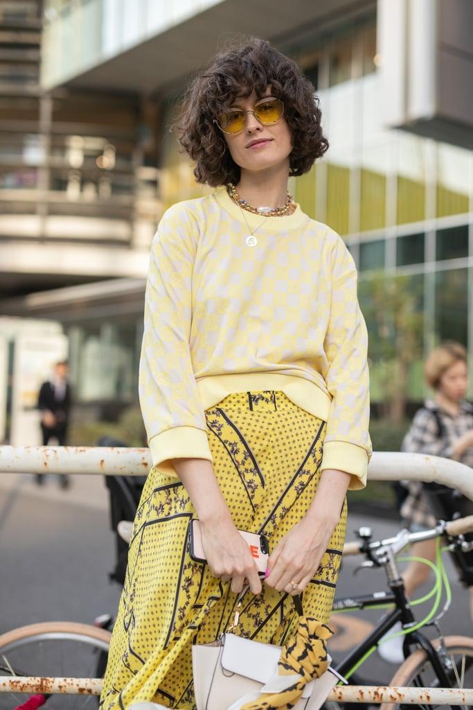 Девушка в желтой легкой юбке и свитшоте