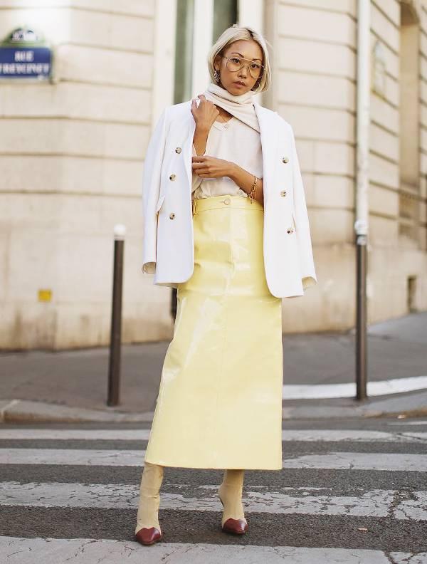 Девушка в желтой юбке карандащ, белый блейзер и ботильоны