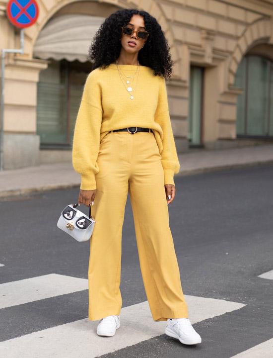 Девушка в желтых брюках, желтый свитер, белые кроссовки и сумочка