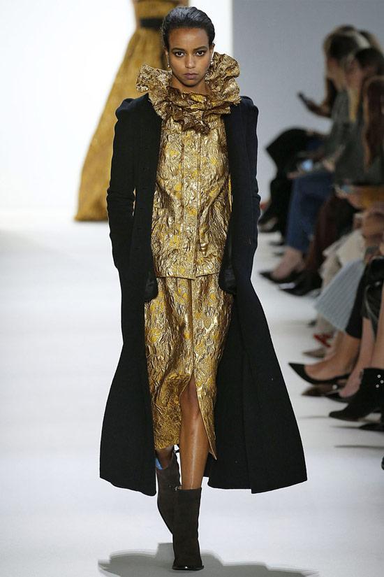 Девушка в золотом костюме с юбкой и черное пальто