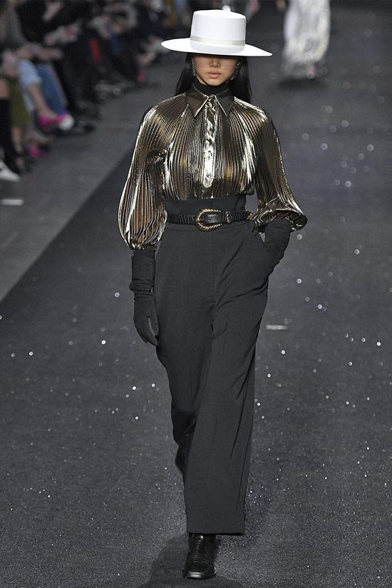 Модель в черных брюках с ремнем и золотая блузка