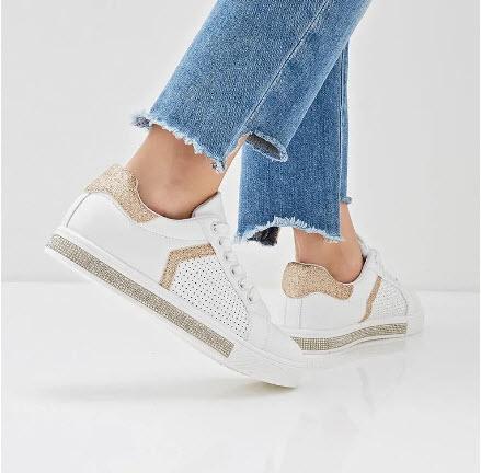 Модель в джинсах и белых кедах с золотой отделкой