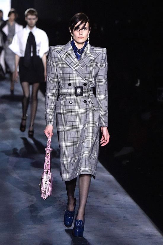 Модель в клетчатом пальто с поясом и синих туфлях