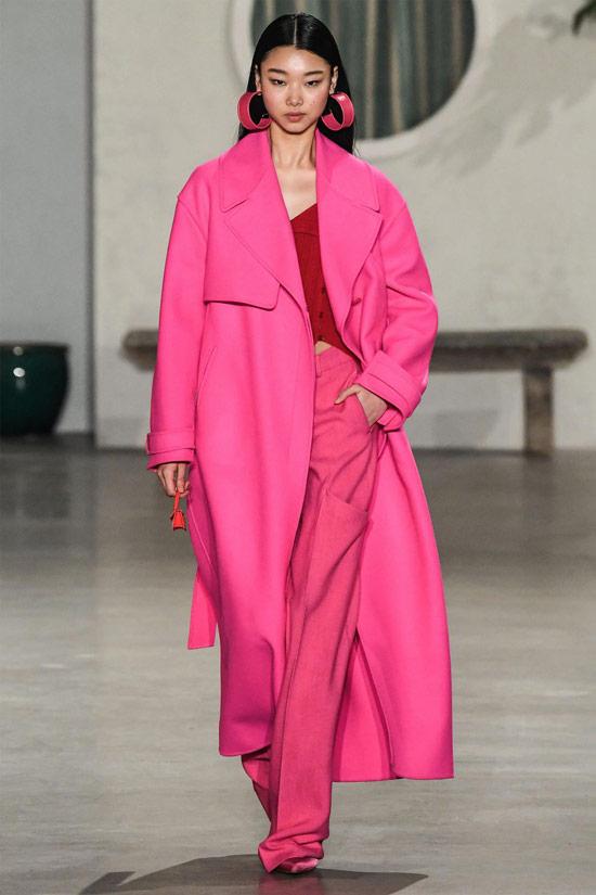 Модель в розовых широких брюках, красный топ и розовое пальто