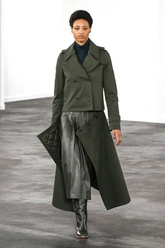 Модель в сером пальто, кожаная юбка миди и сапоги