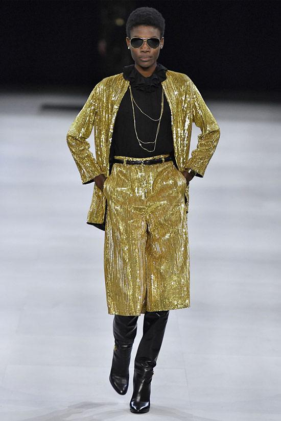 Модель в золотом костюме с бермудами, черная водолазка и сапоги