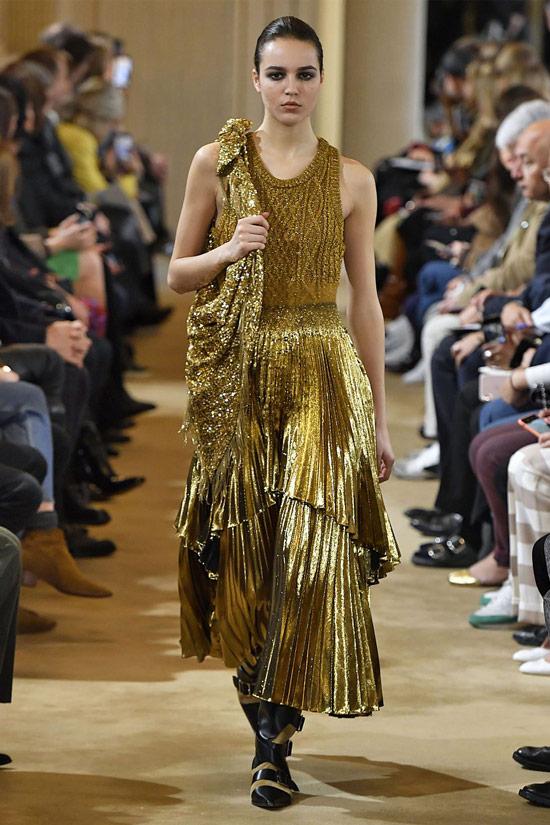 Модель в золотой плиссированной юбке, и топ