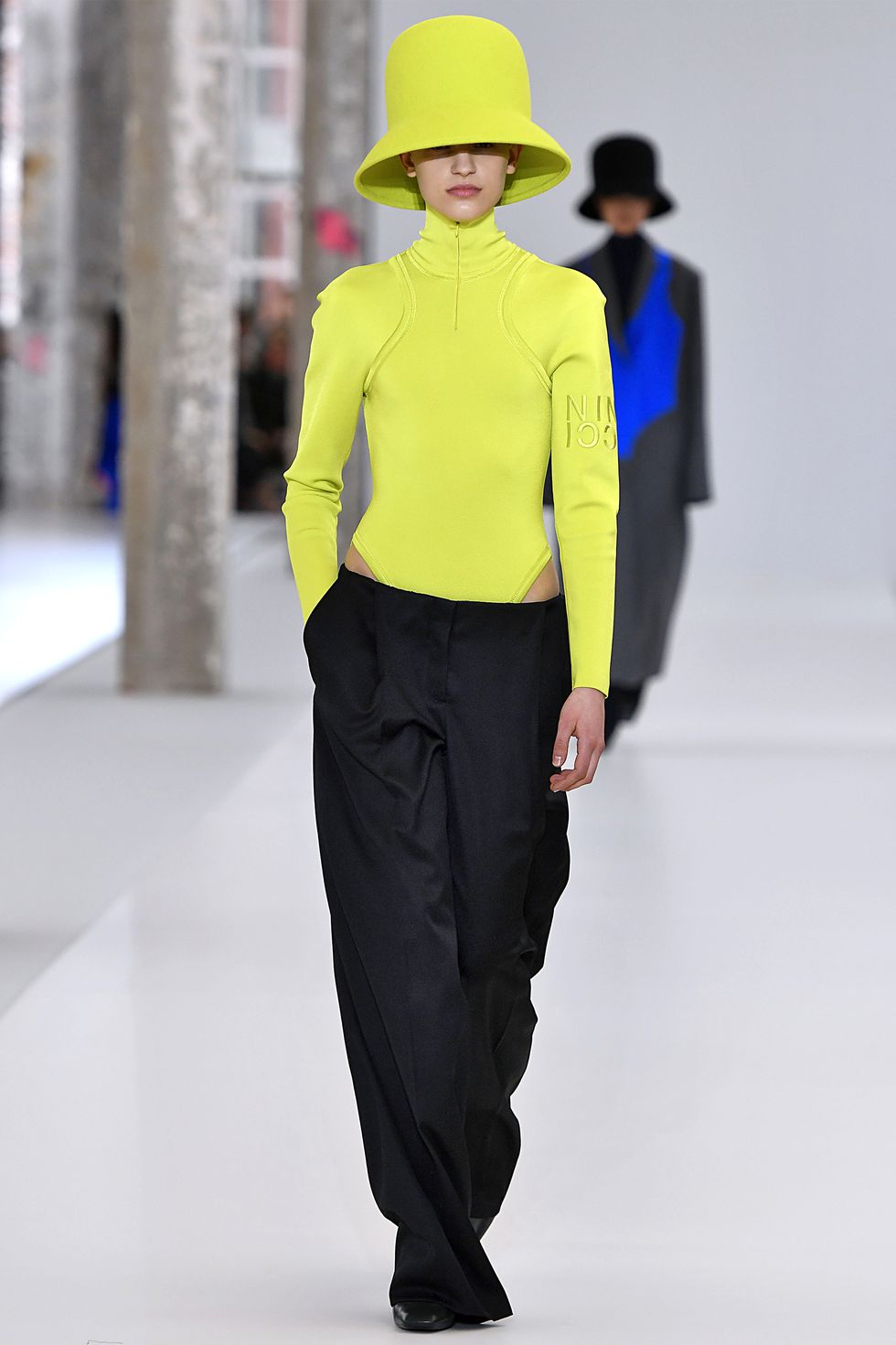 Девушка в черных брюках и неоновй водолазке