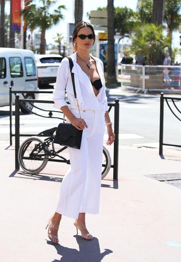 Алессандра Амбросио в белых широких джинсах, белая блузка и черная сумка