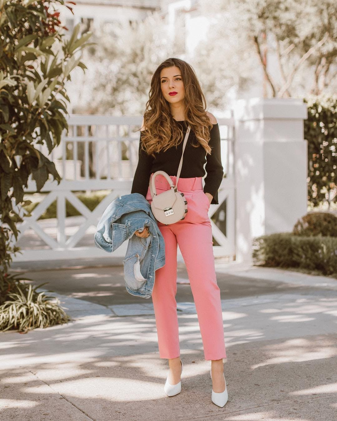 Девушка розовых брюках, черная блузка и белые туфли