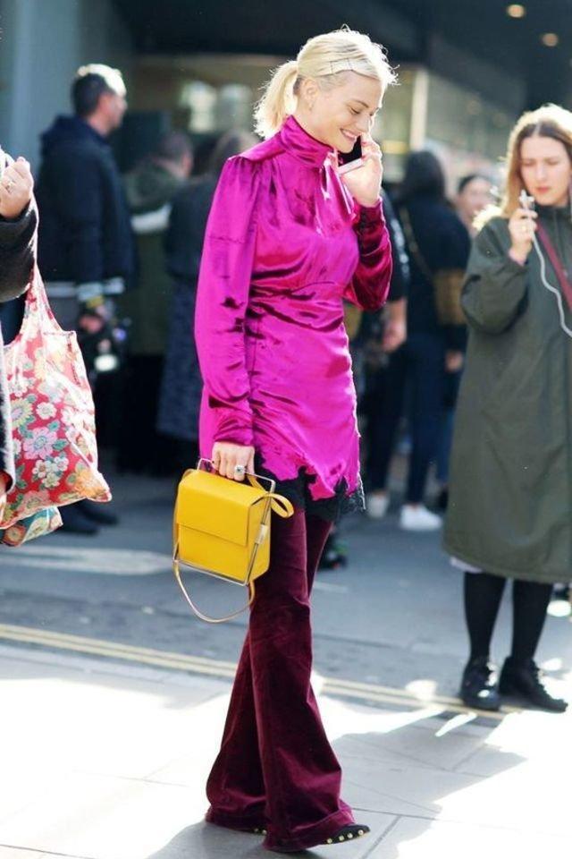 Девушка в бархатных брюках клеш, розовая туника и желтая сумка