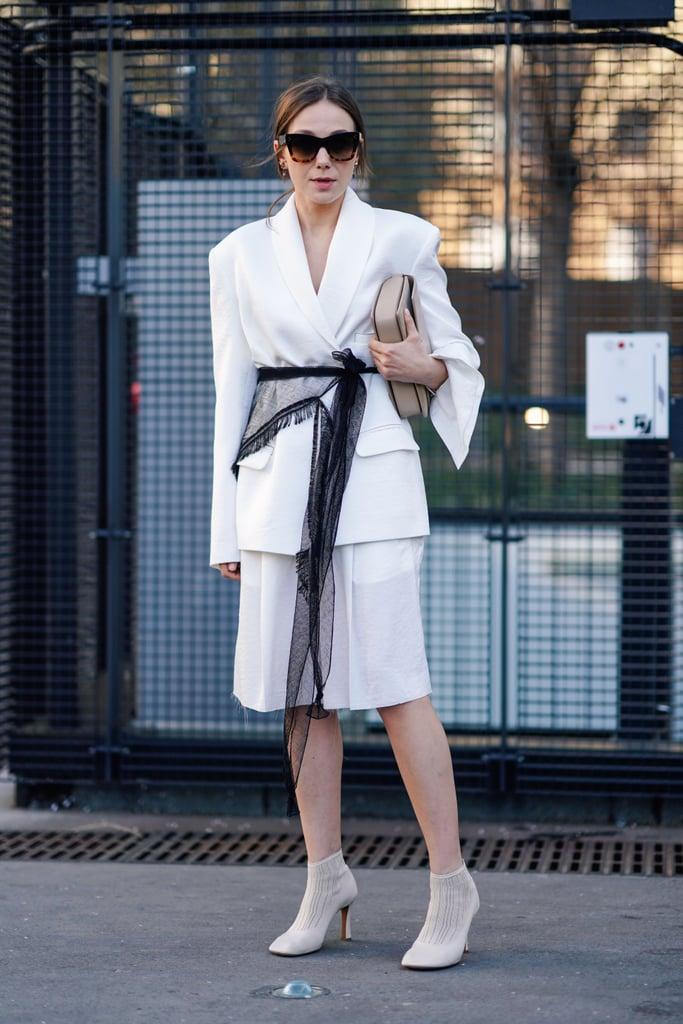 Девушка в белом блейзере с поясом, юбка миди и ботильоны